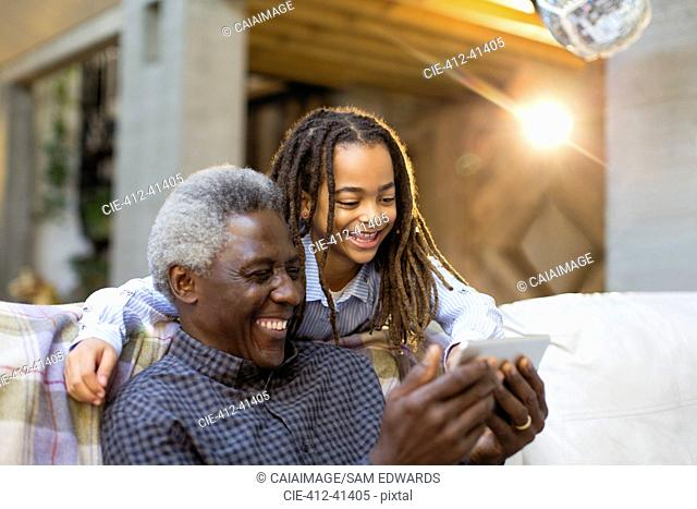 Grandfather and granddaughter using smart phone on sofa
