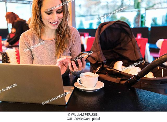 Mid adult woman in cafe texting on smartphone by baby daughter in baby carriage
