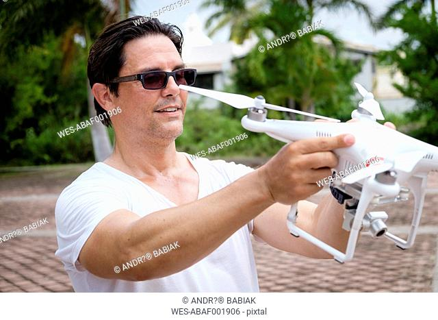 Portrait of man holding drone with camera