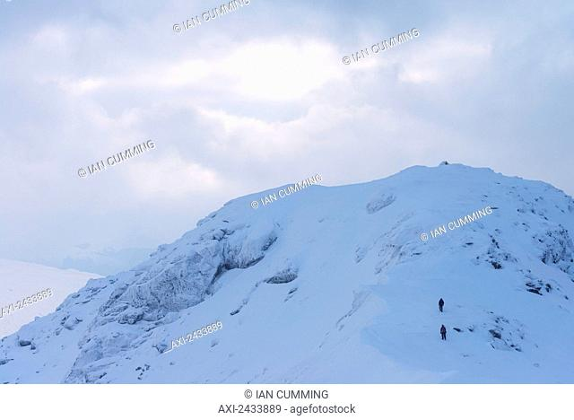Two people approaching summit of Beinn Dorain in snowy, winter conditions, near Bridge of Orchy; Argyll and Bute, Scotland
