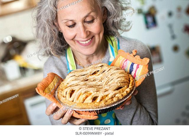 Senior woman holding freshly baked pie