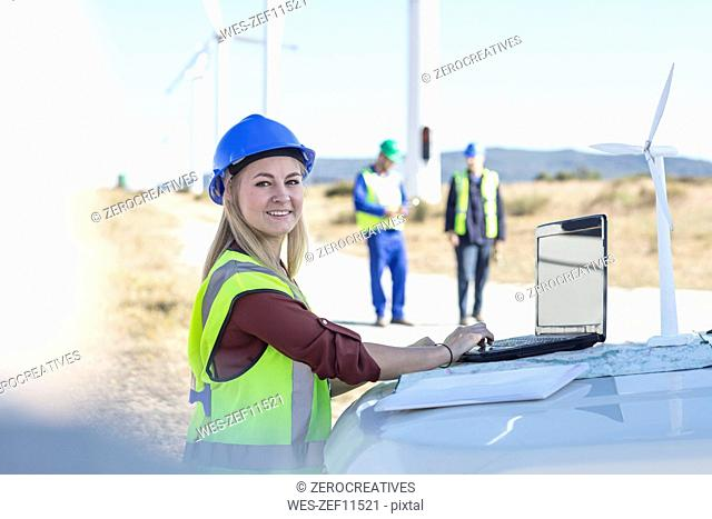 Female engineer working on wind farm, using laptop
