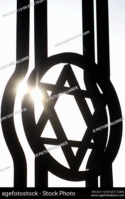 13 November 2020, Saxony-Anhalt, Magdeburg: The sun shines through a Star of David at the gate of the Jewish cemetery. On the cemetery is the memorial for the...