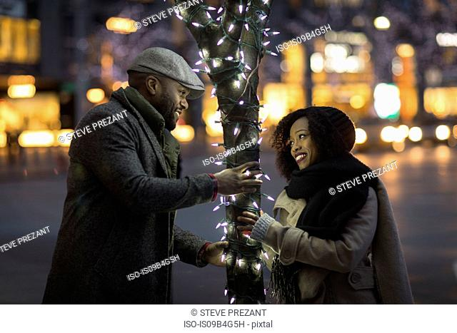 Couple having fun by illuminated tree in city at night, New York, USA