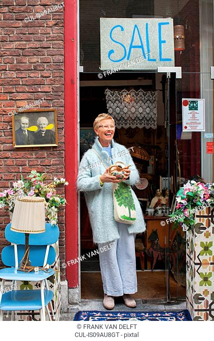 Mature female customer holding teapot outside vintage shop