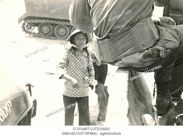 An American soldier climbs down from a military vehicle to approach a Vietnamese woman who is selling soft drinks, during the Vietnam War, 1968. ()