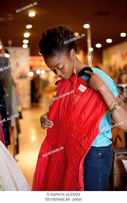 Young woman holding red vintage dress in shop