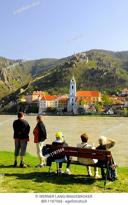 Tourists and pensioners on park benches overlooking the Danube River towards the town and castle ruins of Duernstein, Wachau, Lower Austria, Austria, Europe