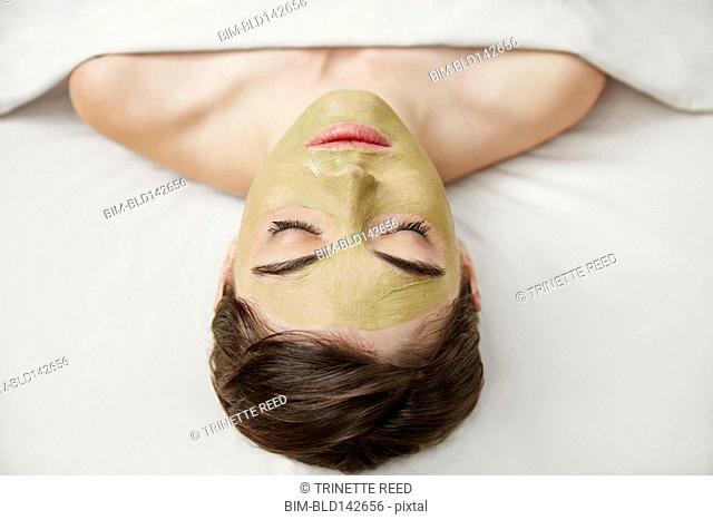Caucasian woman having facial mask in spa