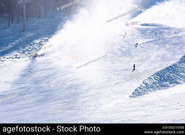 skier riding down the huge snowfield splashing powder snow