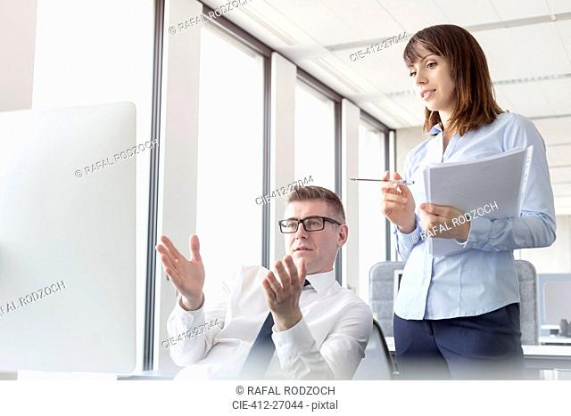 Businessman at computer gesturing and explaining to businesswoman in office