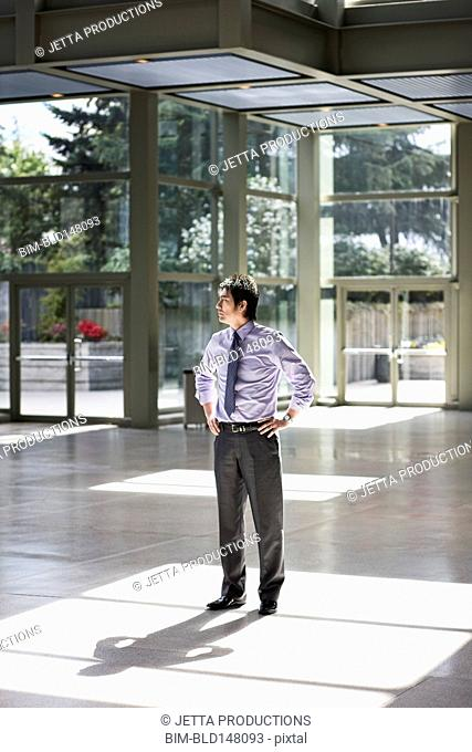 Mixed race businessman standing in lobby