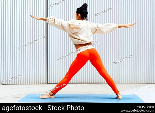 Female athlete standing in warrior position in front of wall