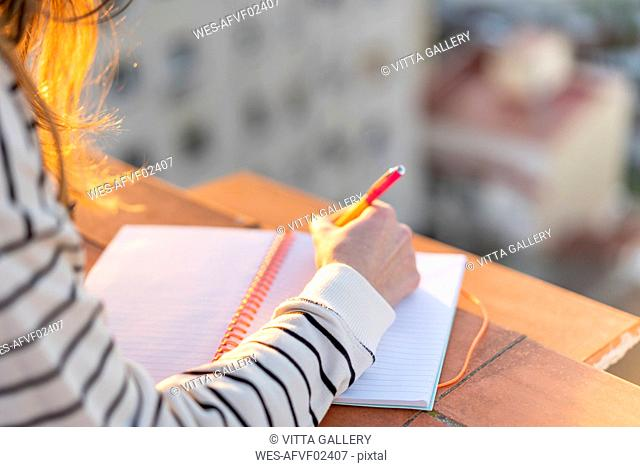 Young woman taking notes on roof terrace at sunset, partial view