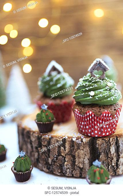 Christmas chocolate muffins with creamy green frosting on a log slice