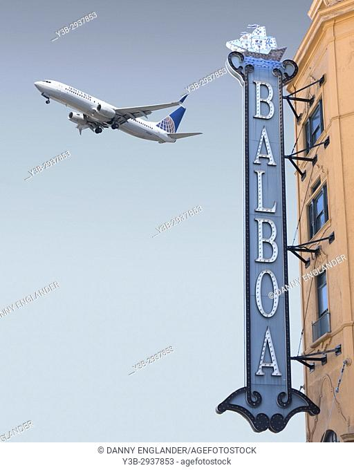 Vintage theater sign in downtown San Diego, CA, with a jet airliner taking off in the background