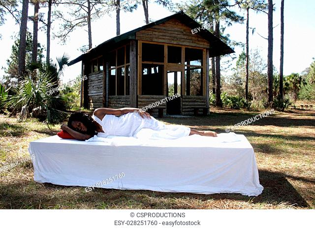 A lovely young woman, wearing a white nightgown, sleeps in her bed in front of her rustic cabin in the forest