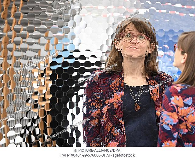 """03 April 2019, Baden-Wrttemberg, Karlsruhe: At the Center for Art and Media (ZKM), a woman is looking at Anish Kapoor's installation """"""""Islamic Mirror"""""""" from..."""