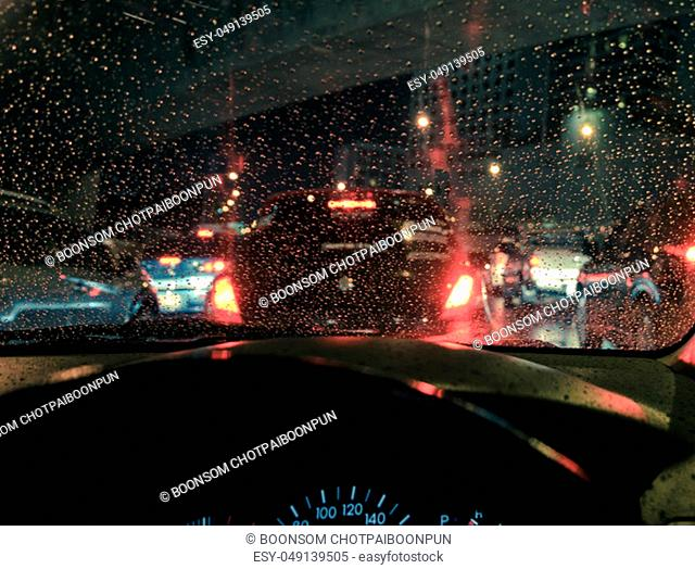 Blurry driving car seen through wet windscreen at night raining. Retro filtered effect image