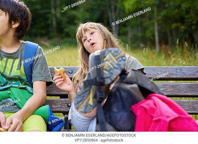 Wanderlust - happy girl taking a break next to a boy during hiking adventure