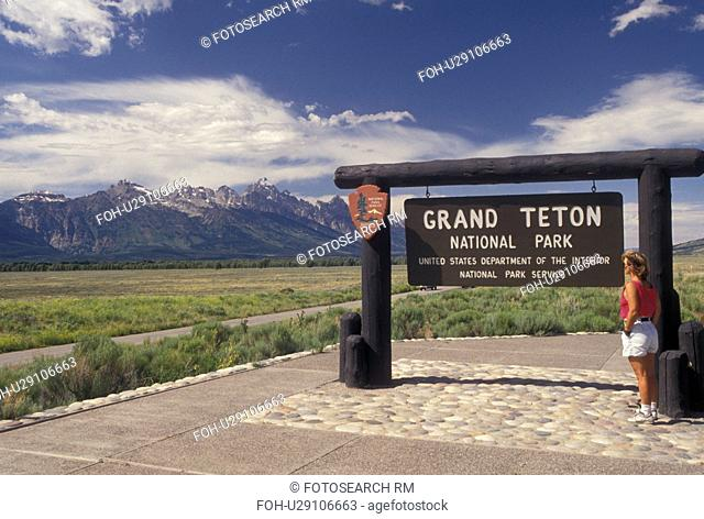 Grand Teton National Park, WY, Wyoming, Woman reading sign at the entrance to Grand Teton Nat'l Park with a scenic view of the Grand Teton Mountains in Wyoming