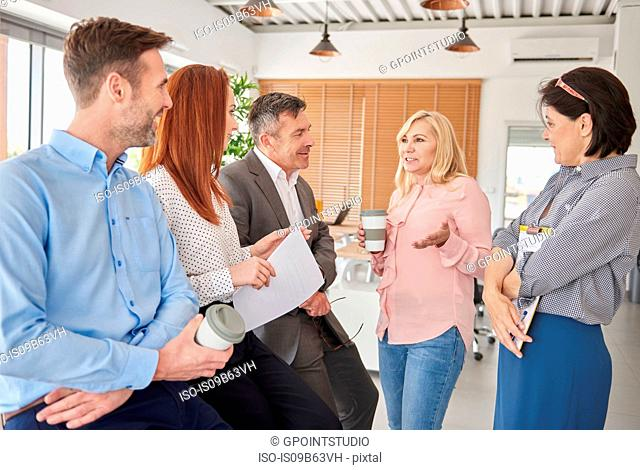 Colleagues standing in office talking