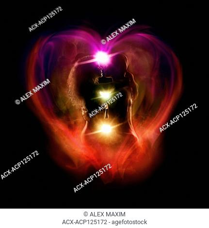 Tantra and Tantric sexuality artistic spiritual concept of a couple making love with the colorful chakra energy flow glowing emanations in a shape of a heart...