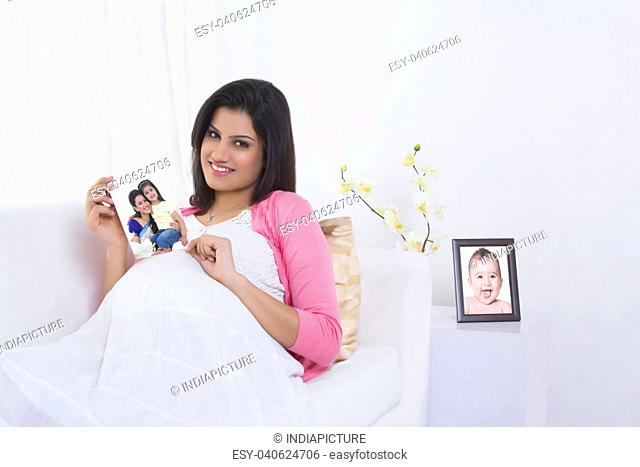Portrait of pregnant woman with a picture