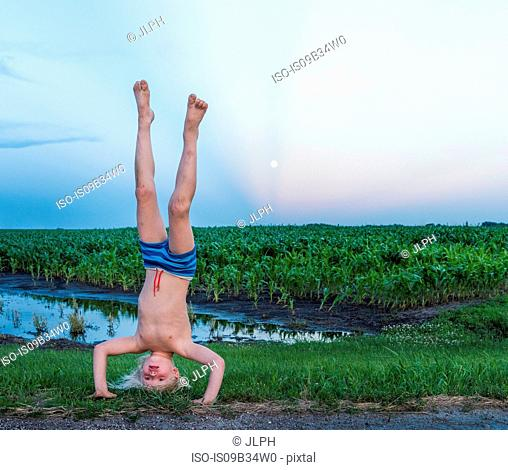 Boy wearing shorts doing handstand in rural area