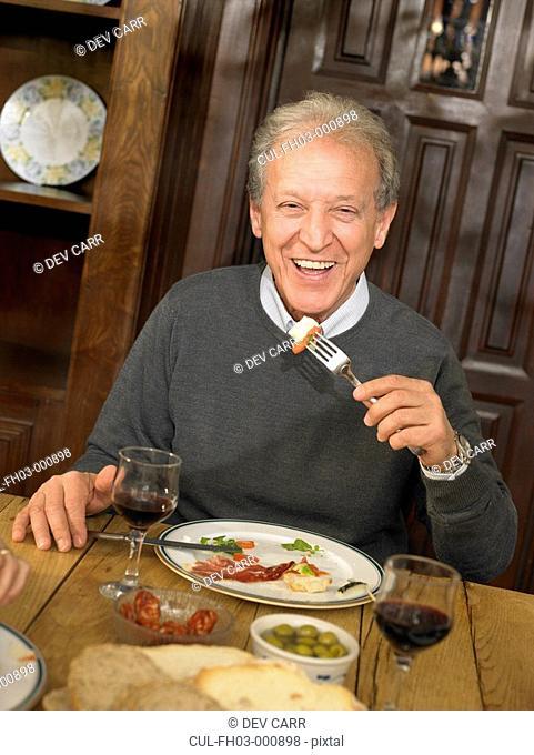 Senior man eating lunch, smiling, portrait