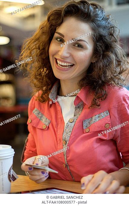 Woman making purchase wiith credit card, smiling, portrait