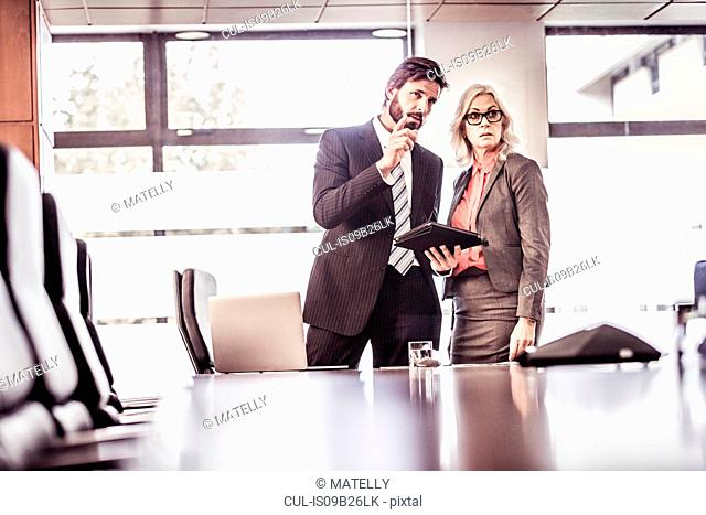 Businessman explaining to businesswoman in boardroom