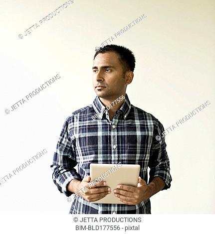 Mixed race businessman holding digital tablet