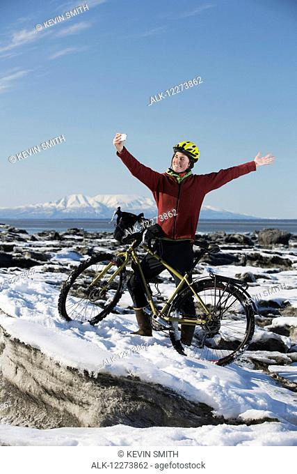 Young woman with her bicycle takes a selfie with a smart phone while standing on frozen ice chunks along the Tony Knowles Coastal Trail, Anchorage