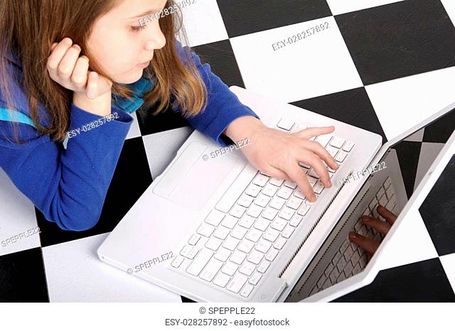 Grade school age girl working on a white laptop computer while lying on the floor