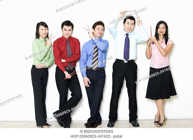 Portrait of five business executives holding chopsticks