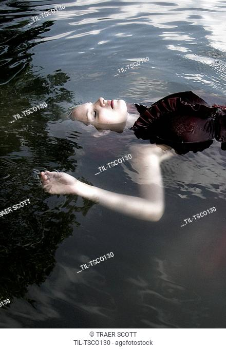 Young woman full body floating clothed in lake