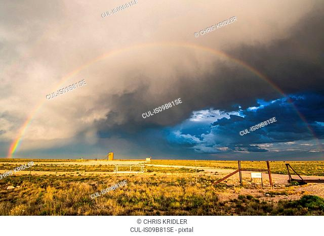 Sunset rainbow amid dramatic clouds over New Mexico desert landscape, USA
