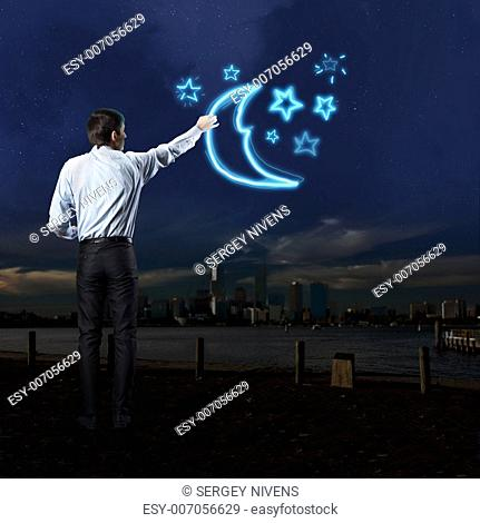 Businessman draws a variety of signs on the dark sky