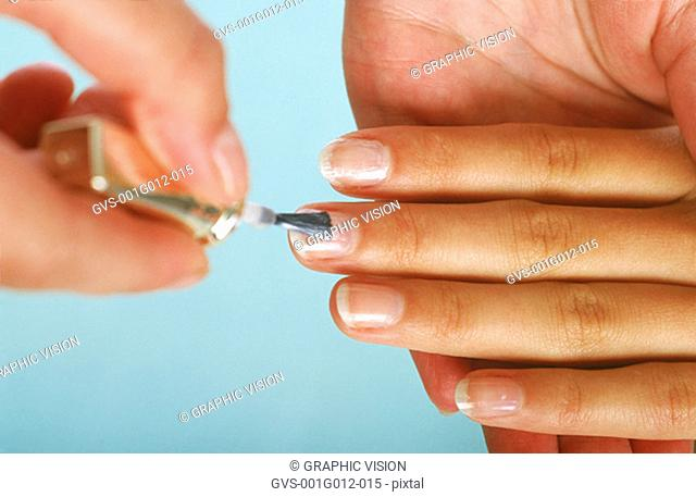 Close-up of a hand painting a woman's fingernails