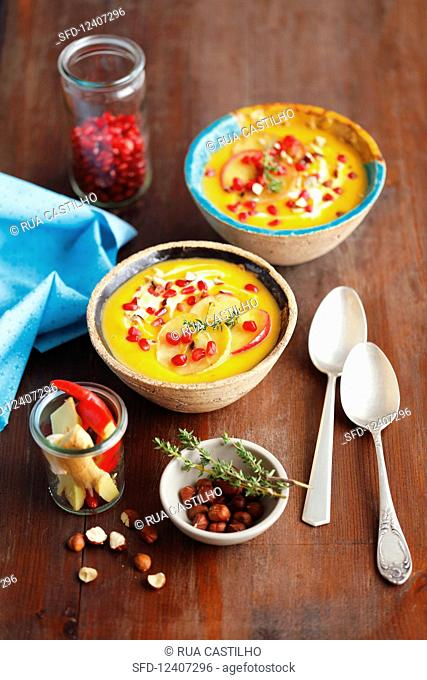 Pumpkin and sweet potatoes cream soup with apples and pomegranate