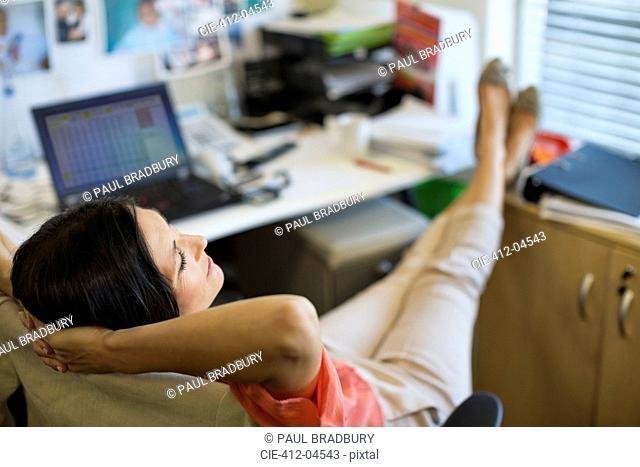 Businesswoman relaxing at desk