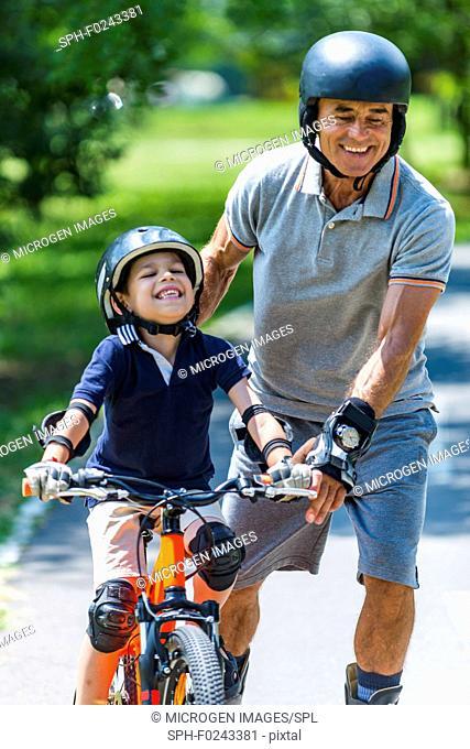 Grandfather and grandson enjoying biking and roller skating