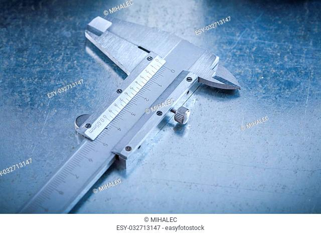Trammel caliper on scratched metallic background horizontal view construction concept