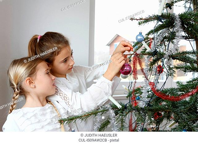 Side view of girls decorating christmas tree with baubles