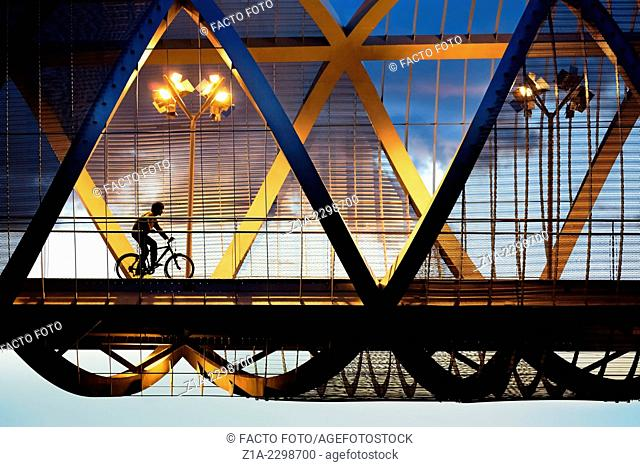 Cyclist passing by the Arganzuela bridge, designed by architect Dominique Perrault. Madrid Rio Park. Madrid. Spain