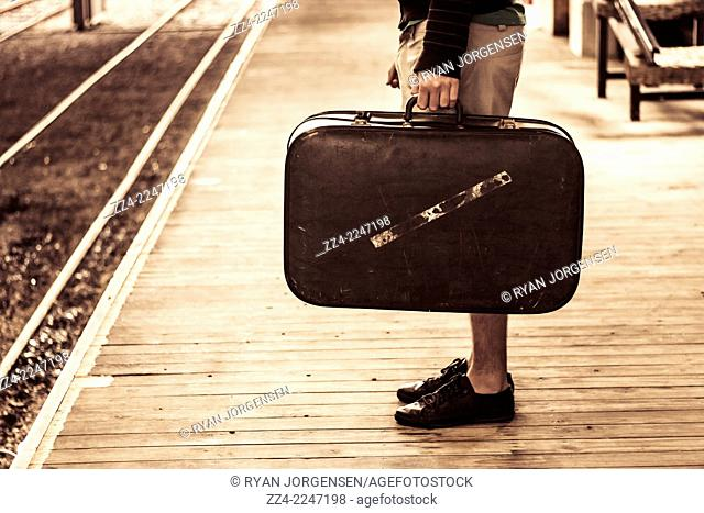 Vintage travel photo of a man carrying antique suitcase on old wooden train platform when on a summer journey. Change of direction