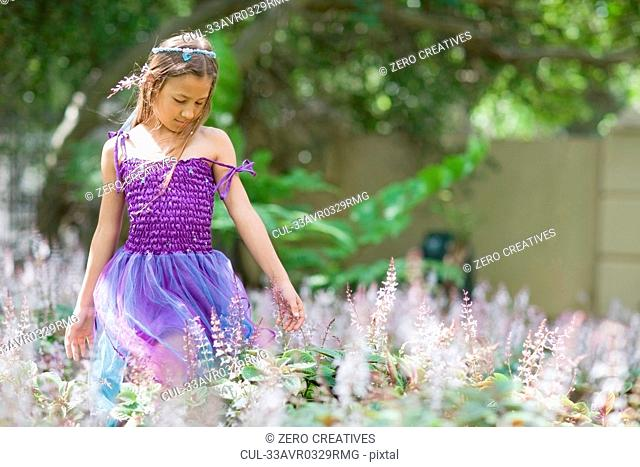 Girl wearing fairy costume in backyard