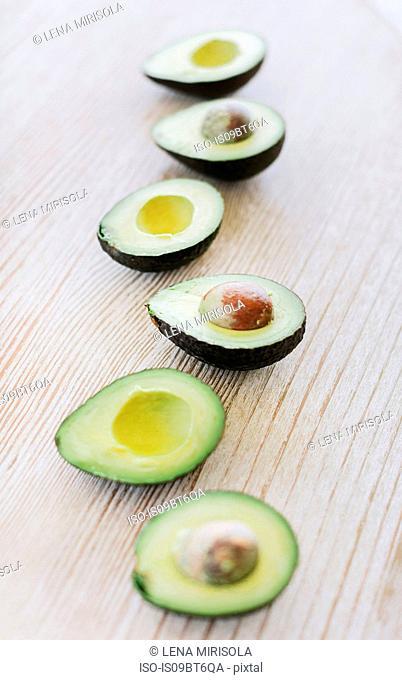Row of halved avocado on wooden table, still life