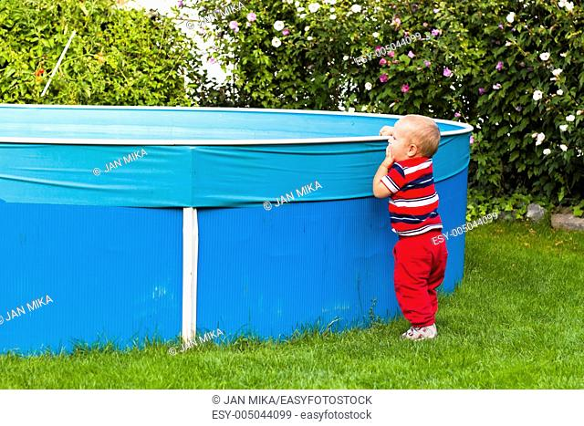 Toddler boy exploring swimming pool in the garden